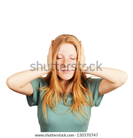 Portrait of a redhaired girl covers her ears with hands. white background.