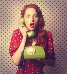 Portrait of a redhead girl with green dial phone on Polka dot background.