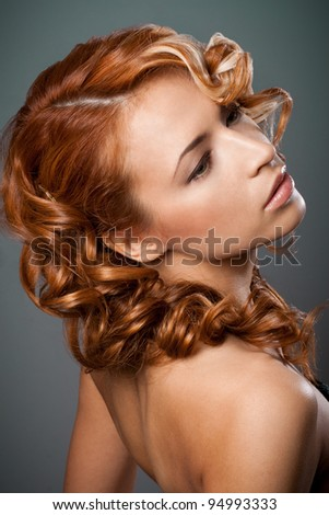 Portrait of a redhead woman with curls from the back