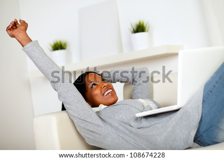 Portrait of a relaxed afro-American woman browsing the Internet on laptop while is lying on sofa at home indoor