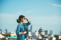 Portrait of a relaxed Asian woman looking forward at the horizon cityscape in the background with her hand on the forehead- copy space