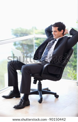 Portrait of a relaxed businessman sitting on an armchair working with a laptop in his office