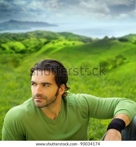 Portrait of a relaxed good-looking young man in beautiful natural setting wearing a green sweater