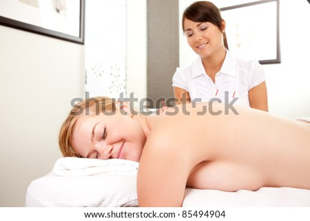 Portrait of a relaxed happy acupuncture patient with needles in the back