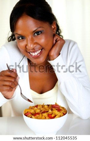 Portrait of a relaxed woman looking at you and having breakfast at soft colors composition