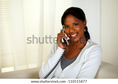 Portrait of a relaxed woman looking at you while talking on phone at home indoor