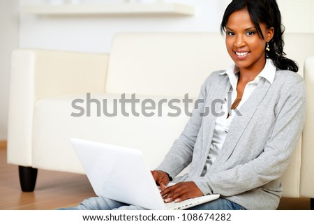 Portrait of a relaxed young woman smiling at you while is sitting on the floor using her laptop at home indoor