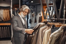 Portrait of a rich mature man. Senior visiting a fashion boutique. Male buy a new exclusive costume.