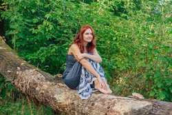 Portrait of a romantic woman with red hair sitting on the old dry fallen tree with bare feet in a wood.