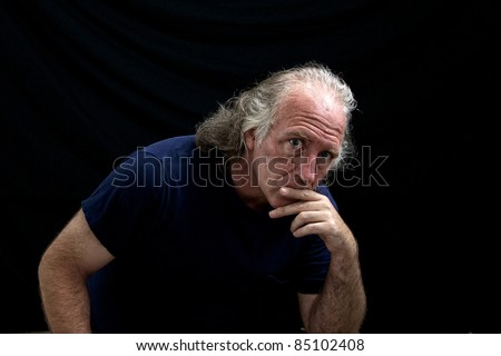 Portrait of a rugged looking man turned towards the viewer and looking thoughtful or judging with his hand to his mouth.
