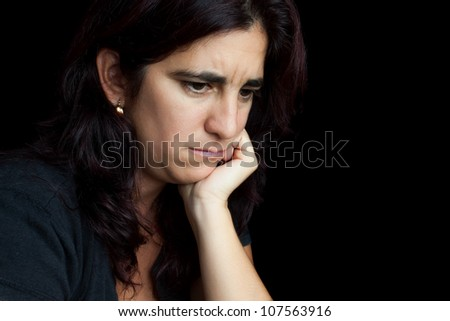 Portrait of a sad and depressed hispanic woman with a thoughtful expression isolated on black