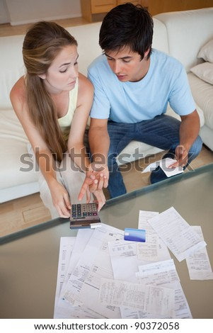 Portrait of a sad couple looking at their receipts in their living room - stock photo