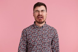 Portrait of a sad crying bearded man in glasses, wearing in colorful shirt, looks unhappy and upset. Isolated over pink background, people and emotions concept.