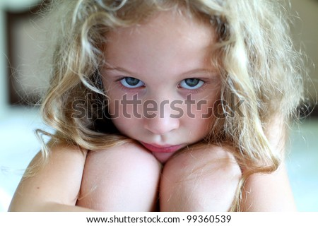 portrait of a sad girl sitting on a bed in the bedroom - stock photo