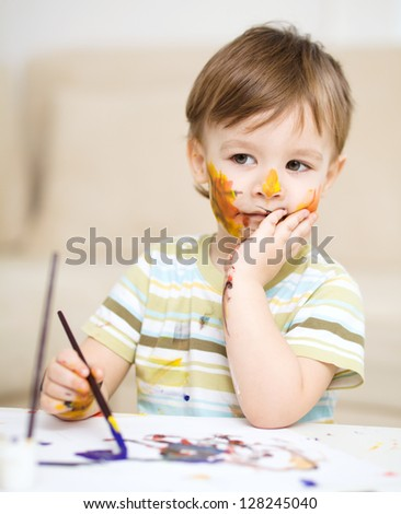 Portrait of a sad little boy messily playing with paints - stock photo