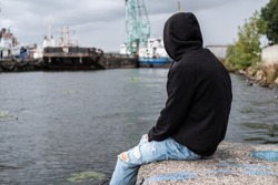 portrait of a sad lonely young guy, a teenager in a black hoodie on the river bank near the port. Problems, loneliness, adolescent psychology, concept.