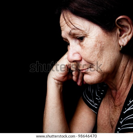Portrait of a sad old woman with a sad nostalgic expression isolated on black