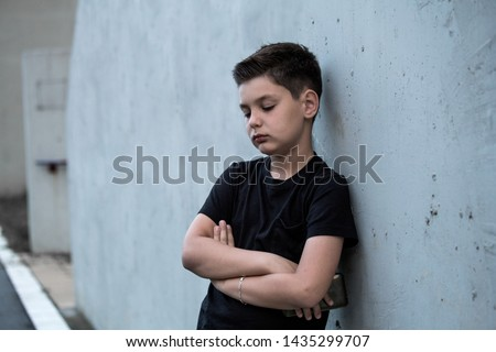 Portrait of a sad teenage boy looking thoughtful about troubles. Pensive teen. Depression, teen depression, pain, suffering