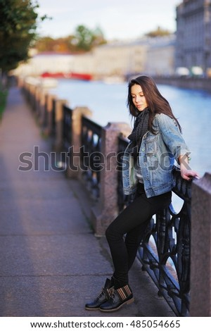 Portrait of a sad teenage girl on the waterfront with unfocused background of the urban landscape, in profile.