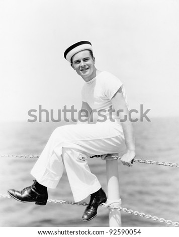Portrait of a sailor sitting on the pole of a boat and smiling