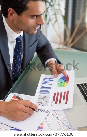 Portrait of a sales person studying statistics in an office