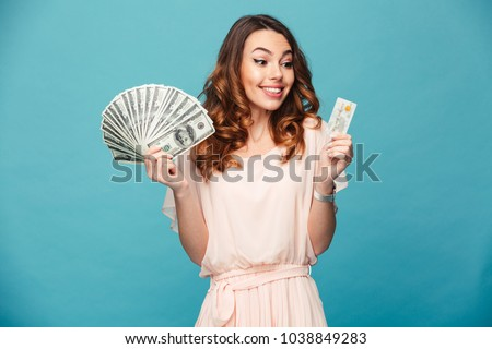Portrait of a satisfied beautiful girl wearing dress holding money banknotes and credit card isolated over blue background