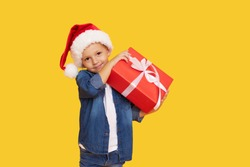Portrait of a satisfied little child boy in christmas Santa hat. laughing isolated over yellow background. Holds a gift box. Preparing for the New Year holidays