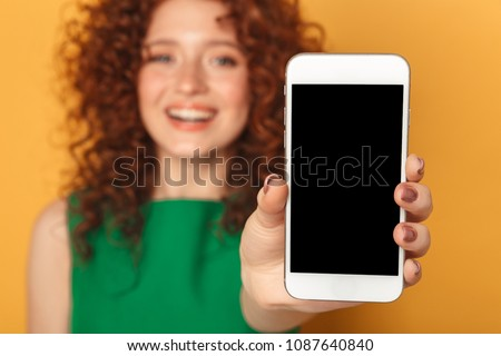Portrait of a satisfied redhead woman in dress showing blank screen mobile phone isolated over yellow background