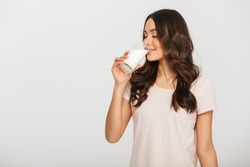 Portrait of a satisfied young asian woman drinking milk from the glass isolated over white background