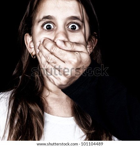 Portrait of a scared girl being abused by an adult man who covers her mouth with his hand (only his hand is visible, the rest is hidden in the shadows) - stock photo