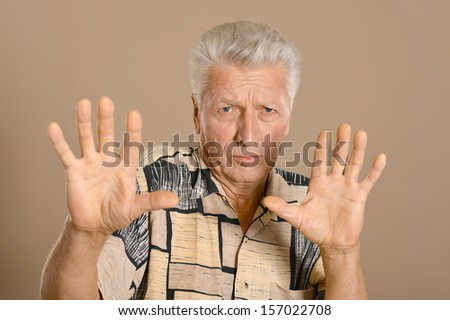 Portrait of a scared senior man on brown