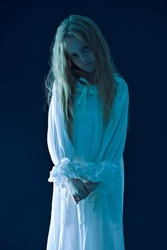 Portrait of a scary little girl ghost in a white nightgown on  dark blue  background. Halloween.