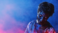 Portrait of a scary zombie boy teenager in blue and crimson smoky lighting. Halloween, horror movie.