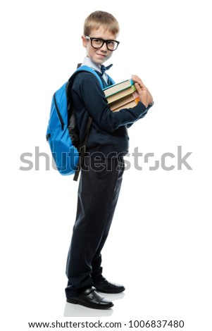 portrait of a schoolboy with a ball and textbooks on a white background in the studio #1006837480