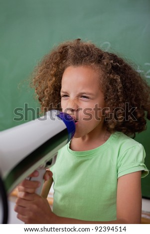 Portrait of a schoolgirl screaming through a megaphone in a classroom