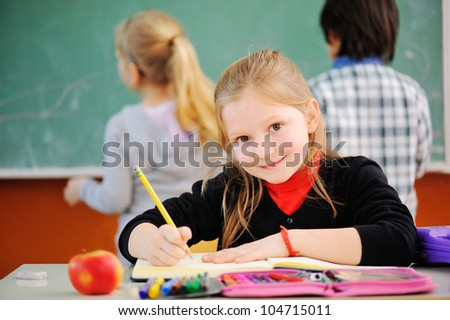 Portrait of a schoolgirl with pencil looking at camera during lesson, friends in background