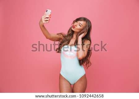 Portrait of a seductive young woman dressed in swimsuit taking selfie with mobile phone isolated over pink background
