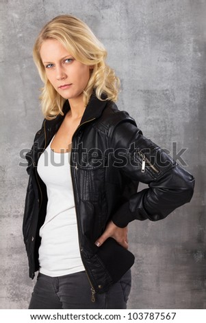 Portrait of a self-confident modern woman with hands on hips looking at the camera. Studio shot against a gray background.
