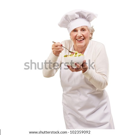 portrait of a senior cook woman eating a salad over a white background