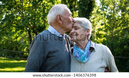 Portrait of a senior couple are hugging and kissing with affection as a sign of their forever love and respect to each other in a green park in a sunny day.