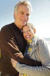 Portrait of a senior couple standing outdoors hugging one another looking at the camera smiling.