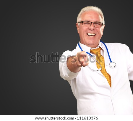 Portrait Of A Senior Doctor Pointing On Black Background