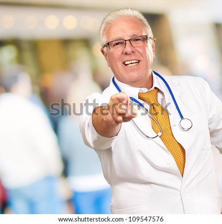 Portrait Of A Senior Doctor Pointing, outdoor