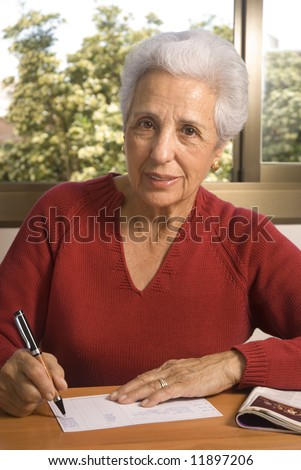 Portrait of a senior lady writing at home