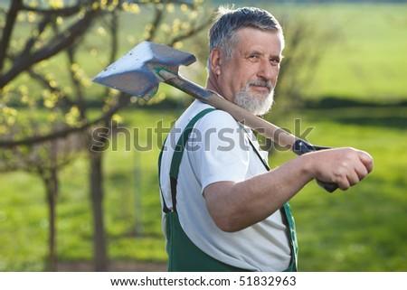 Portrait of a senior man gardening in his garden/orchard