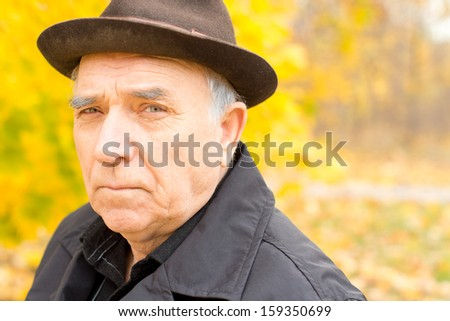 Portrait of a senior man in a warm hat and overcoat outdoors in a colourful yellow forest with copyspace