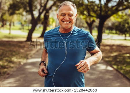 Photo of  Portrait of a senior man in fitness wear running in a park. Close up of a smiling man running while listening to music using earphones.