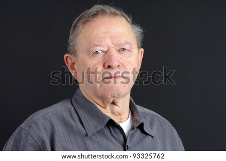 Portrait of a senior man looking very serious, sad or depressed looking at camera with blue eyes, great details, shot in studio over black.