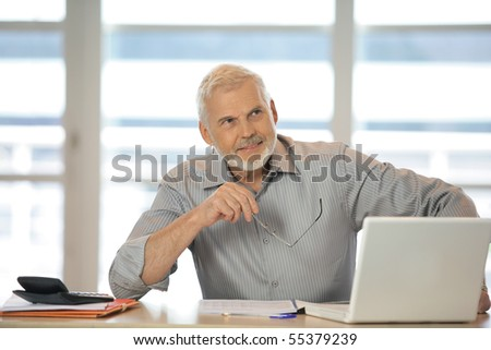 Portrait of a senior man sitting at a desk in front of a laptop computer