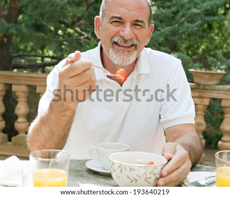Portrait of a senior man sitting at a table having breakfast in a luxury hotel garden on holiday. Mature people eating and drinking healthy food and relaxing, smiling. Outdoors lifestyle.